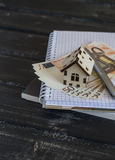 Model house, Euro banknotes, notepad on dark wooden background. Stock Image