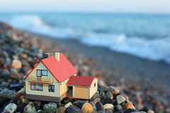 Model of house with garage on stony beach Stock Photography