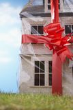 Model house gift-wrapped with red ribbon and bow close-up Stock Image