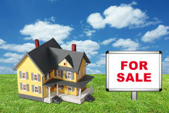 Model house on green grass with for sale sign Royalty Free Stock Image