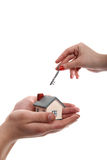 Model of a house in hands and key in another Royalty Free Stock Photos