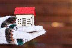 Model of house at hands, outdoors. Protecting and isolating house. Winter. Real estate and property concept. Small miniature of. House at hands in winter gloves royalty free stock photos