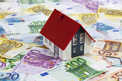Model house on heap of euro notes Stock Photo