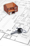 Model house and key on plans Royalty Free Stock Image