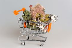 Model of house with keys in the shopping cart on gray Stock Images