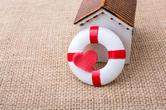 Model house and a life preserver with heart shaped. Model house and a life preserver with red heart shaped on it Stock Photo