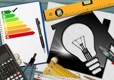 Energy Efficiency Rating - House with Light Bulb. Model house with a light bulb and a energy efficiency rating on the desk with a calculator and work tools royalty free stock images