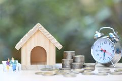 Model house with Miniature couple standing on coins money and glass bottle with alrm clock on natural green background, Save money royalty free stock image
