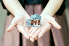 A model house model is placed on The Hands of Asian Business Girl.using as background business concept and real estate concept wit. H copy space for your text or Stock Photo