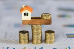 Model house and money coins balancing on a seesaw, Property real estate investment ideas, Concept of risk house mortgage, loan royalty free stock photo