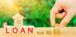 Model of the house, money and the inscription `Loan`. Buying a home in debt. Family investment in real estate and risk management. Concept. Loan for a mortgage royalty free stock photo