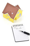 Model house and notepad with pen Royalty Free Stock Images
