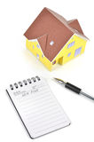 Model house and notepad with pen Royalty Free Stock Photo