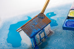 Model house and painting brush in foamy water Stock Photo