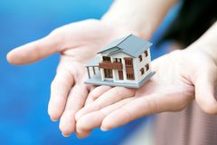 A model house model is placed on The Hands of Asian Business Girl ้.using as background business concept and real estate concept. With copy space for your Stock Photos