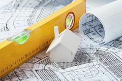 Model house on prints. Small simple white model house on prints with a yellow leveler Royalty Free Stock Photos
