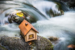 Model house beside rushing water Royalty Free Stock Photography