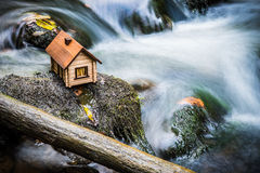 Model house beside rushing water Stock Images