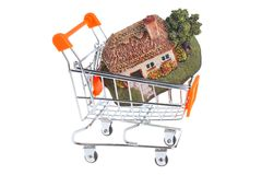 Model of house in the shopping cart isolated on white Stock Photos