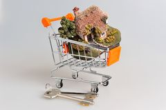 Model of house in the shopping cart next to keys on gray Stock Photography