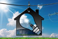 Model House with Solar Panel and Light Bulb. 3D illustration of a model house with a light bulb on a blue sky with clouds, sun rays and a solar panel inside Royalty Free Stock Photo
