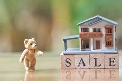 A model house model and Teddy Bear is placed on wood word sale.as background business concept and real estate concept Stock Photo
