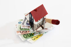 Model house with trowel on wad of notes Stock Photos