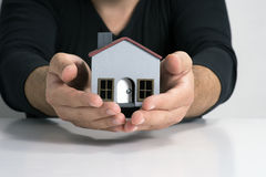 Model house in two hands. Model house on a white background and on two hands Stock Image