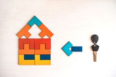Model house from wooden puzzle with key. Model house made from wooden puzzle with key on white wooden background.. Property and mortgage concept royalty free stock photography