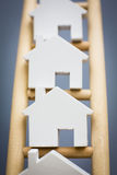 Model Houses On Rungs Of Wooden Property Ladder Stock Photography