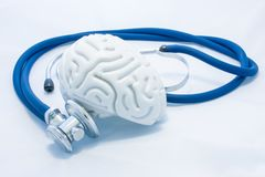 Model of human brain with convolutions and blue stethoscope are on white uniform background. Concept photo health or pathological. Condition of human brain stock image