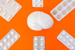 Model of human brain surrounded by six blister packs with white pills inside six-pointed star in corners of image on orange backgr. Ound.  Concept art photo of Stock Images