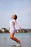 Model jumping in the lake. Beautiful girl modeling at the beach Royalty Free Stock Photos