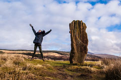 Model jumping next to a standing stone in Scotland, UK. Model jumping next to a standing stone with Scottish landscape in the background. Scotland, UK Stock Images