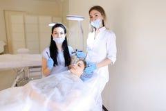 Model krijgende het tatoeëren wenkbrauwen bij de kosmetiekkabinet door dermatoloog Stock Fotografie