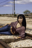 Model laying on Train Tracks. Pretty model laying on train tracks at the Hawaiian Railway on Oahu stock image