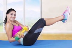 Model lifting dumbbell and her leg on mat Royalty Free Stock Photos