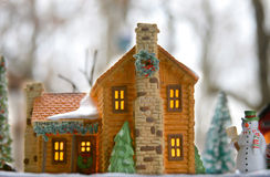 Model log cabin winter scene. Lighted model log cabin scene with snowman and trees Stock Images