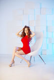 Model with long hair in red dress with chair. Waves Curls Hairst Stock Photos