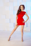 Model with long hair in red dress with chair. Waves Curls Hairst Royalty Free Stock Photo