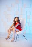 Model with long hair in red dress with chair. Waves Curls Hairst Royalty Free Stock Images