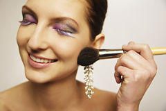 Model make-up blush. Teen model with colorful eyelash and eyeshadow applying blush on stock image