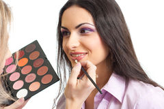 Model make up lips applying with brush and palette Stock Image