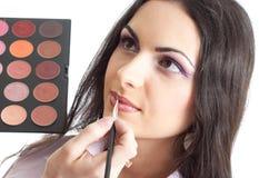 Model make up lips applying studio isolated Stock Photo