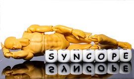 A model man and a word syncope. A model man lying on the floor with alphabet letterS spelling the word syncope, symbolizing a condition that need urgent medical Royalty Free Stock Photo