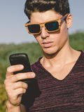 Model man portrait with wooden sunglasses outdoors. Man is using Stock Image