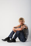 Model man sit in jeans and shirt Royalty Free Stock Photos