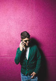 Model man talking with a smart phone over fuchsia background Royalty Free Stock Image
