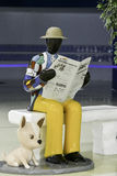 The model of a man in travel attire reads a newspaper in korean royalty free stock photos
