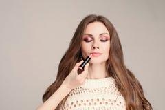 Model met gesloten ogen die terwijl stilist die make-up doen zitten royalty-vrije stock foto's